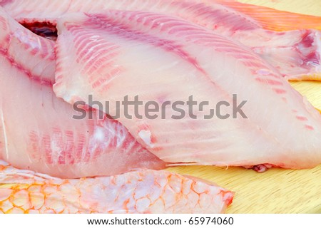 Red tilapia on wood chopping block.