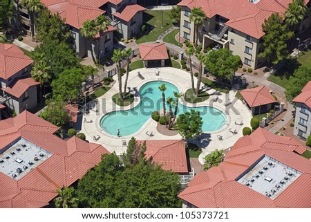 Red Tile Apartment Rooftops and Swimming Pool - stock photo