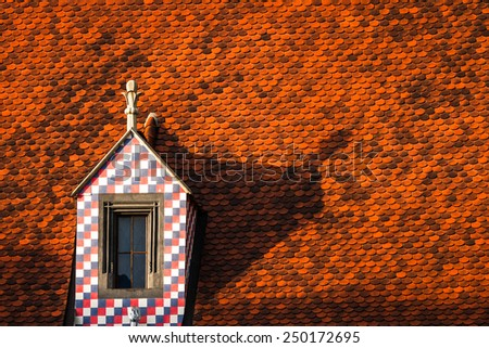 Red tile roof with a tower with a square texture in the center of Bratislava, Slovakia closeup - stock photo