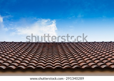 red tile roof with blue sky - stock photo