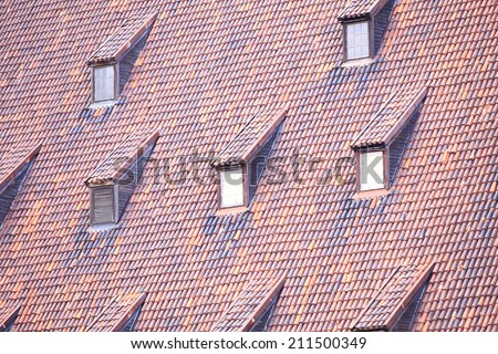 Red tile roof with many windows old town Gdansk Poland - stock photo