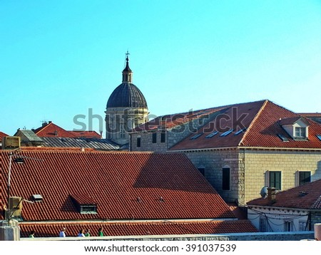 Red tile roofs in the medieval walled city of Dubrovnik, Croatia, with the dome of the Dubrovnik Cathedral in the distance - stock photo