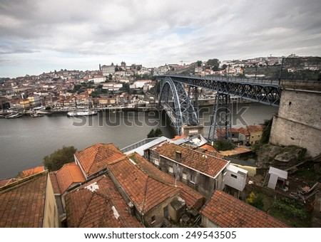 Red tiled roofs, metal bridge, old houses and the river Douro in Porto. Low clouds. - stock photo
