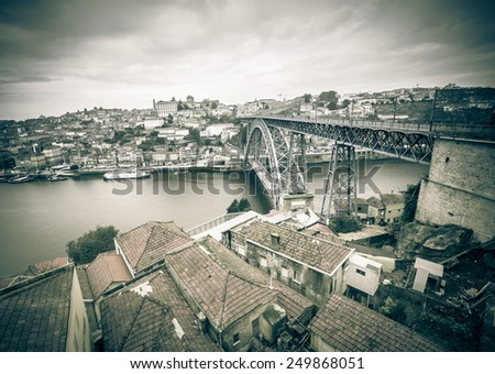 Red tiled roofs, metal bridge, old houses and the river Douro in Porto. Low clouds. Toned. - stock photo