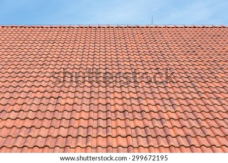 Red tiles roof background with blue sky - stock photo