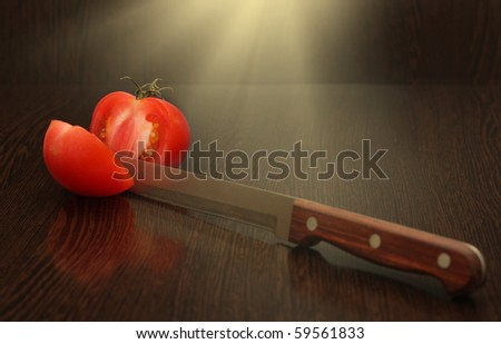 Red tomato and  knife on wooden  background. - stock photo
