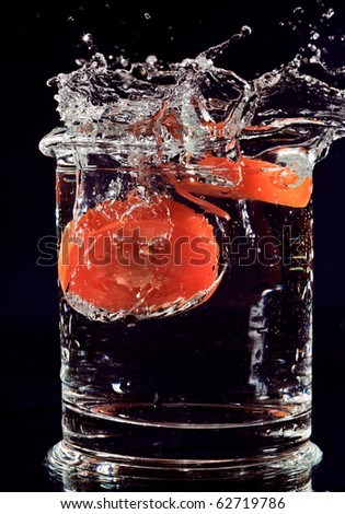 Red tomato falling down in glass with water on deep blue