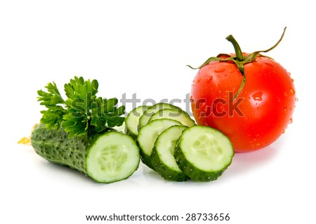 Red tomato, green cucumber and parsley on a white background