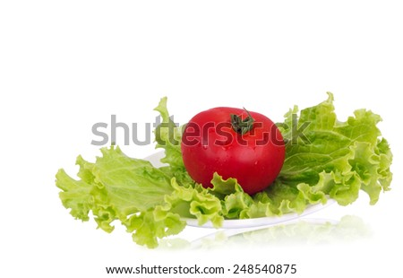 Red tomato lying on the green lettuce leaf on the plate - stock photo