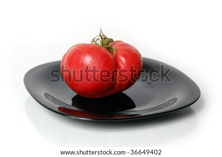Red tomato on a black plate isolated on white background