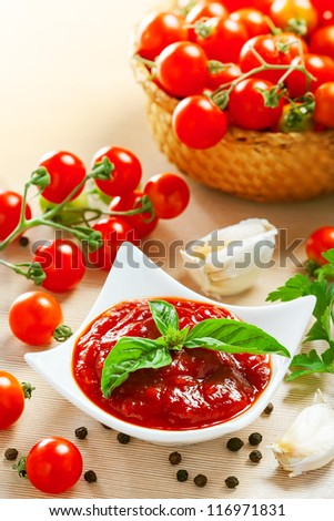 Red tomato sauce in a pan and ingredients - stock photo