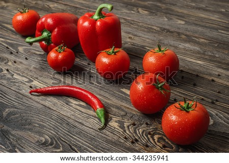 Red tomatoes, chilly pepper and paprika standing in a diagonal line on an old brushed wooden table - stock photo