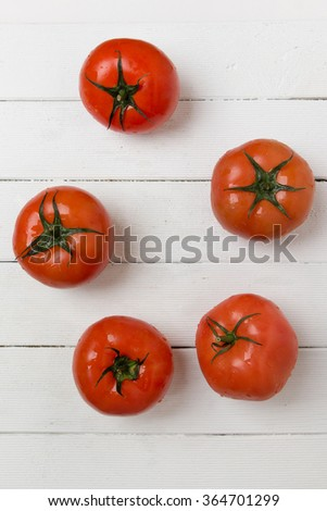 Red tomatoes fruits isolated on a white wooden background. - stock photo