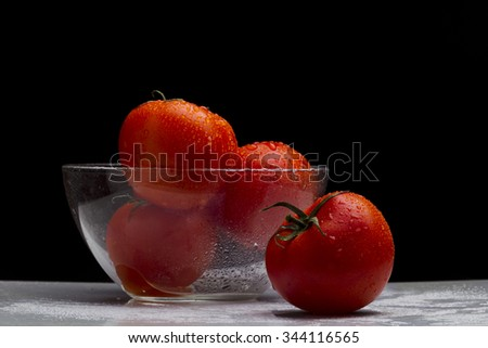 Red tomatoes in a glass bowl, the water on black and white background, studio lighting, a short pulse