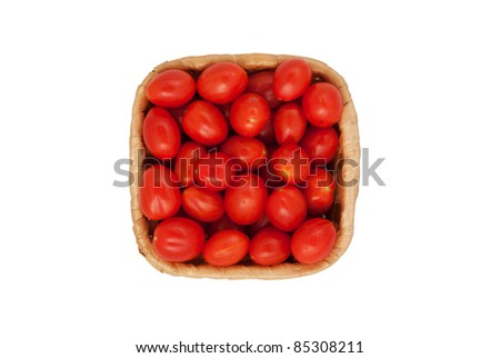 Red tomatoes in a wattled basket on a white background - stock photo