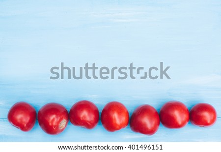 Red tomatoes on a blue wooden background. Flat lay. - stock photo