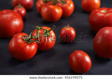 red tomatoes on black wooden background. close up