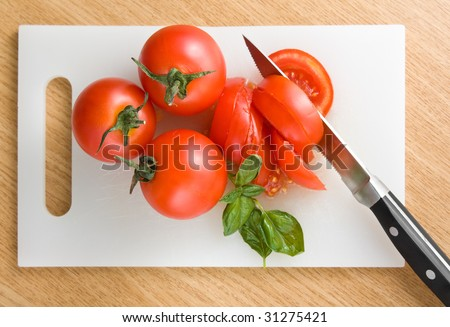 Red tomatoes on hardboard with a knife - stock photo