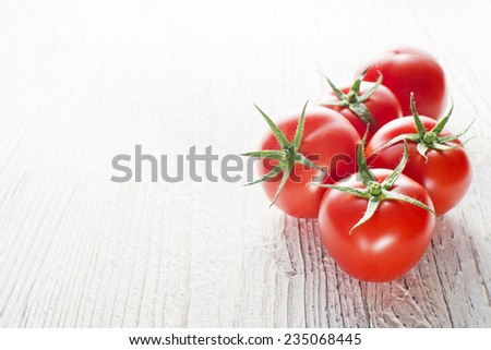 Red tomatoes on white wooden table with space for text - stock photo