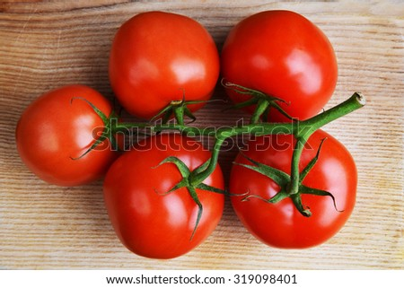 red tomatoes with branch on wooden background - stock photo