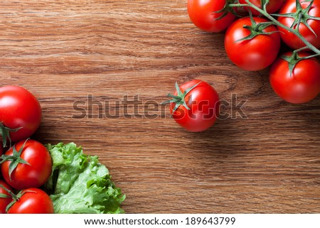 red tomatoes with green salad on wood - stock photo