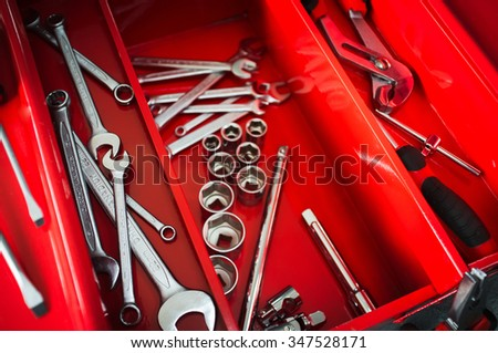 Red toolbox with metal work wrench kit of repairman. Chrome tools for automobile repair in garage - stock photo
