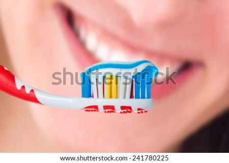 Red toothbrush with blue two color toothpaste with human smile background. Photo of dental hygiene and health maintenance - stock photo