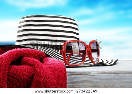 red towel hat and red sunglasses on blue desk