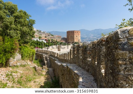 Red Tower (Kizil Kule) and the ruins of the fortress wall. The Mediterranean coast. Alanya. Turkey - stock photo