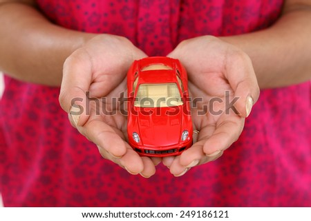 Red toy car in hands - stock photo