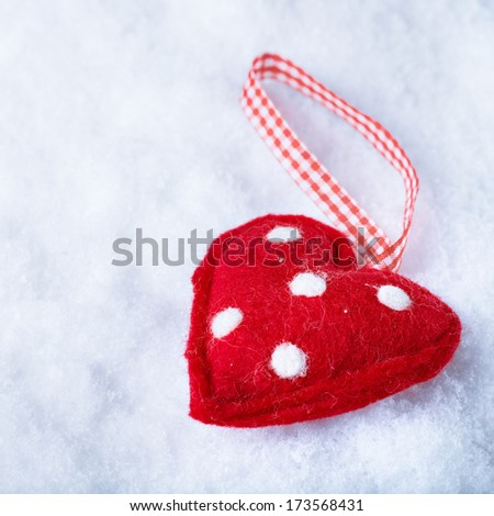 Red toy suave heart on a frosty white snow background. Love and St. Valentine concept.