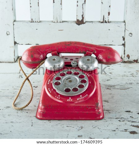 Red toy telephone on light blue wooden vintage chair - stock photo