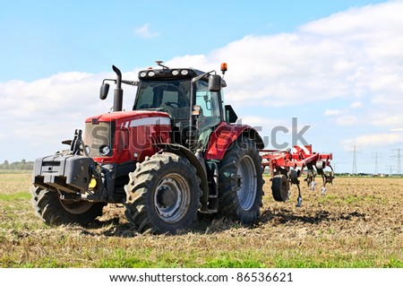 red tractor during cultivation with plough - stock photo