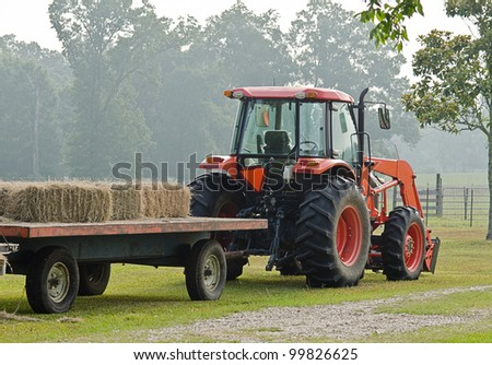 Red tractor hauling bales of hay - stock photo