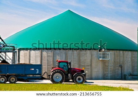 Red tractor in front of a biogas plant