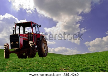 Red tractor in green field with cloudy sky.