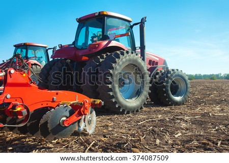 Red tractor in the field on a sunny day - stock photo