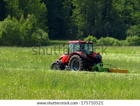 Red tractor on a green field