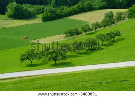 red tractor on a green field with trees and a country road - stock photo
