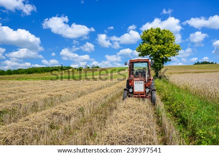 Red tractor on wheat field after harvest in summer, Poland