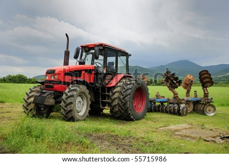 Red tractor parked on a grass field - stock photo