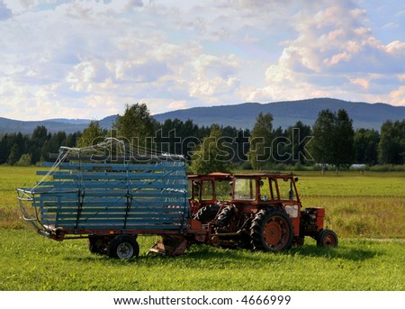 red tractor parked on a summer filed