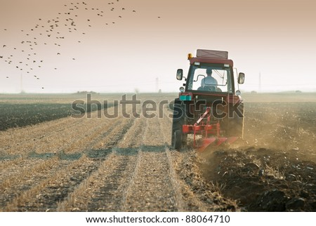 Red Tractor Plowing in dusk - stock photo