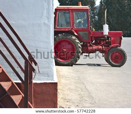 red tractor resting in a white wall - stock photo