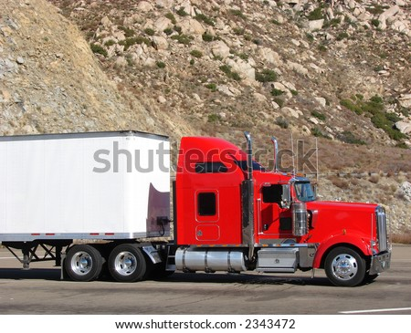Red tractor truck with white trailer on mountain road parking lot with rocky cliff