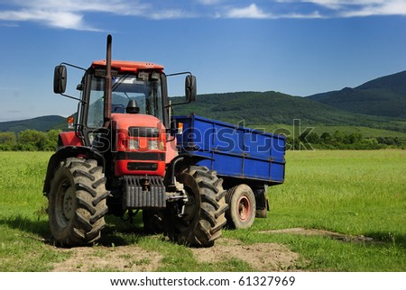 Red tractor with blue trailer on a grass field - stock photo