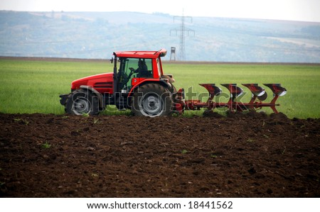 Red tractor working at field - stock photo