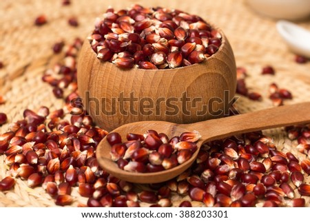 Red traditional corn on a straw background.