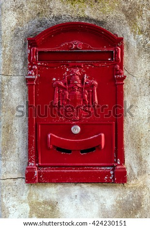 Red traditional post box on the old wall - stock photo