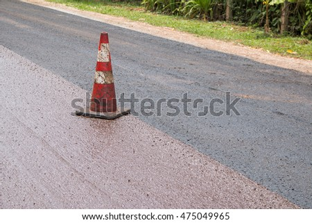 Red traffic cone on construction road.